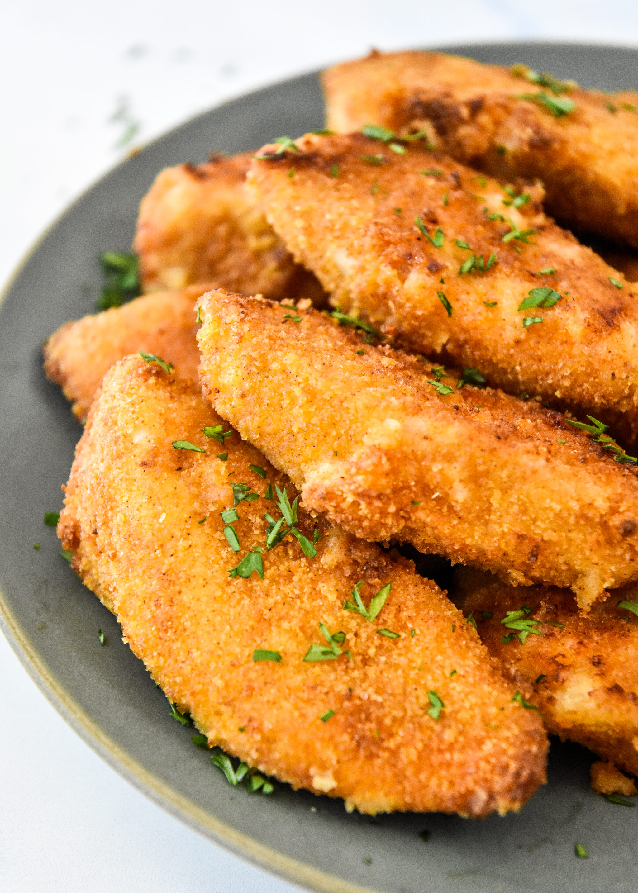 delicious air fryer breaded chicken tenders on a plate ready to eat.