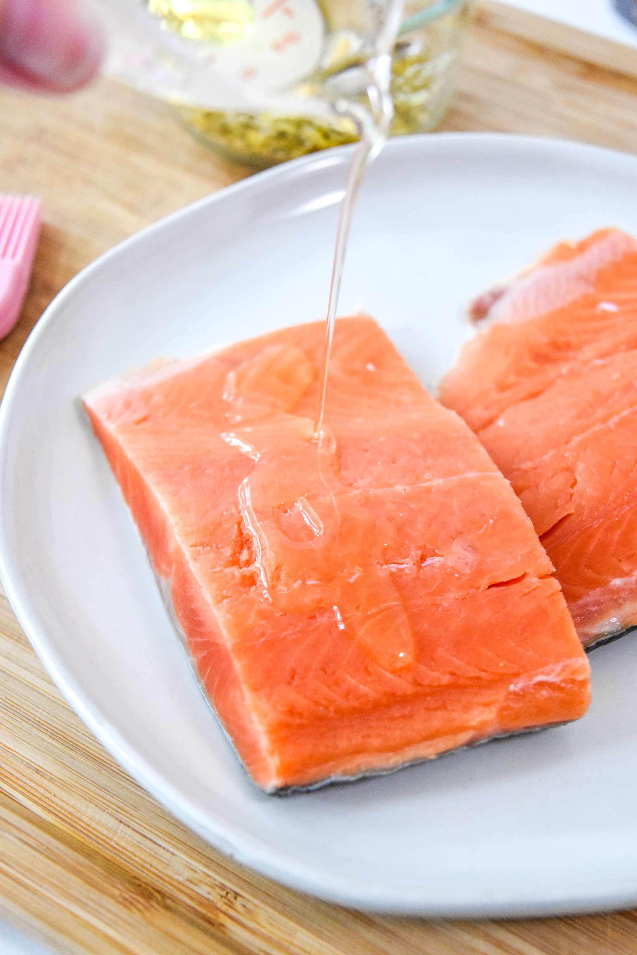 pouring oil on the salmon to coat both sides.