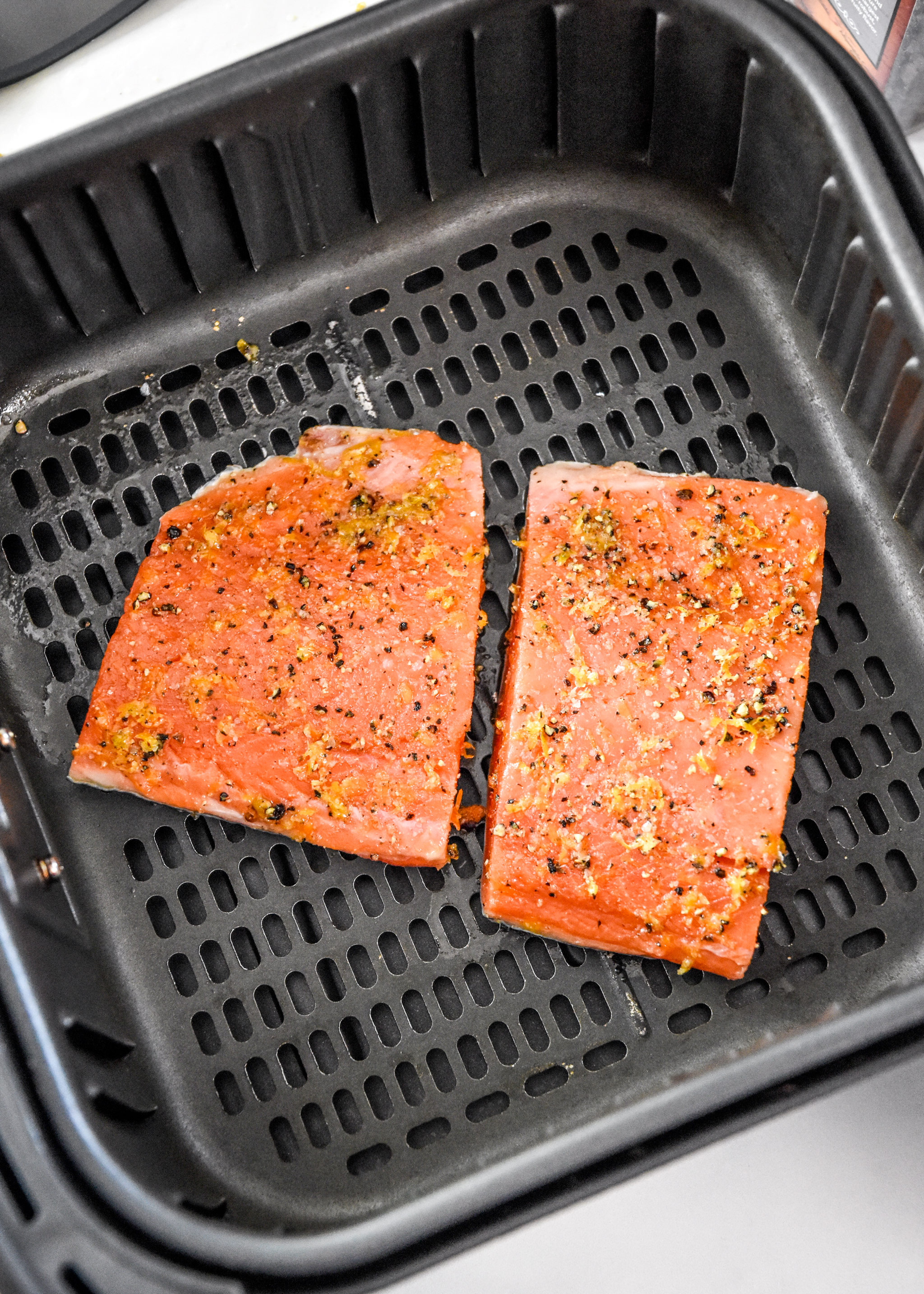 raw salmon in the air fryer basket about to be cooked.