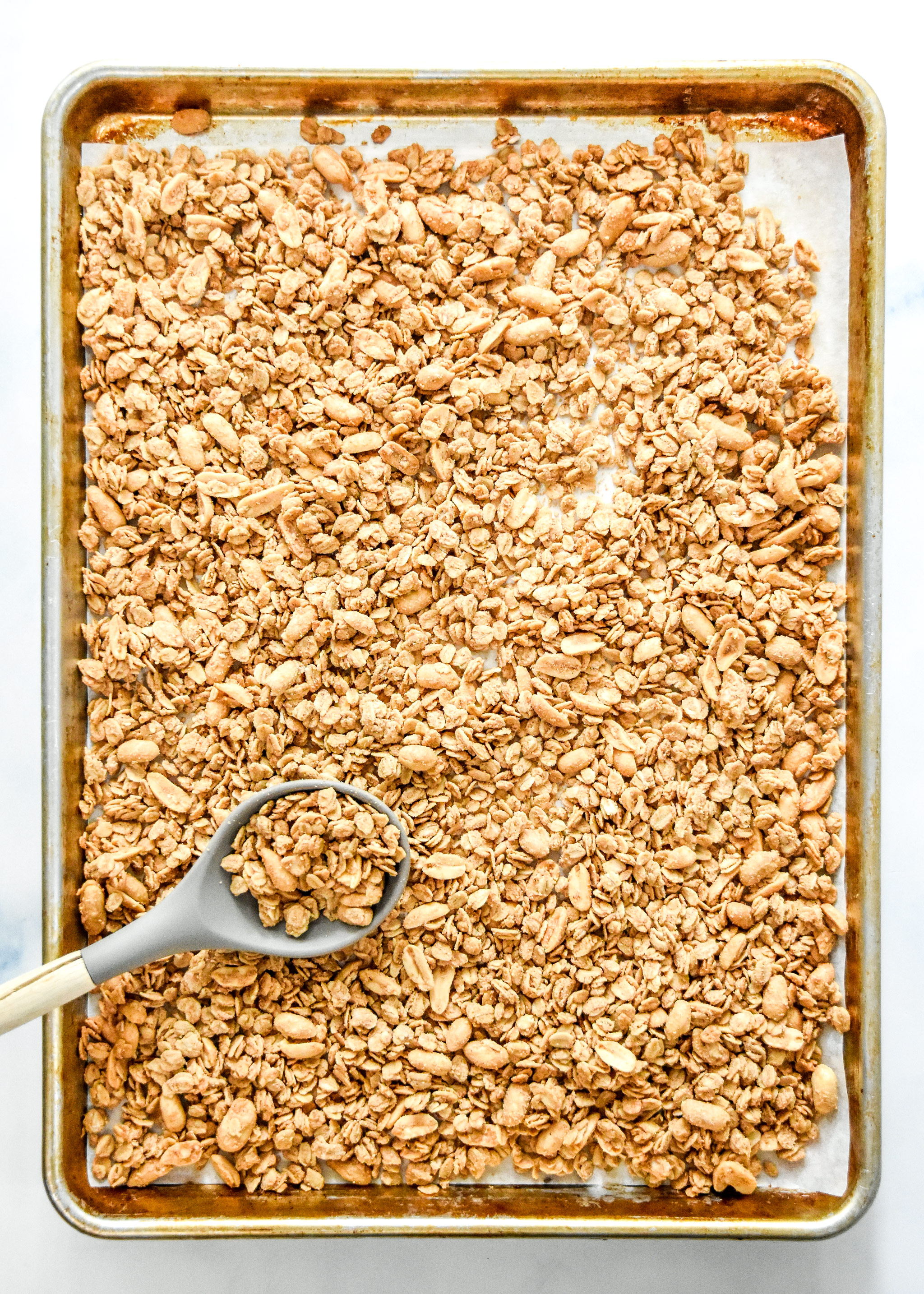 cooked peanut butter granola on a sheet pan with a spoon.