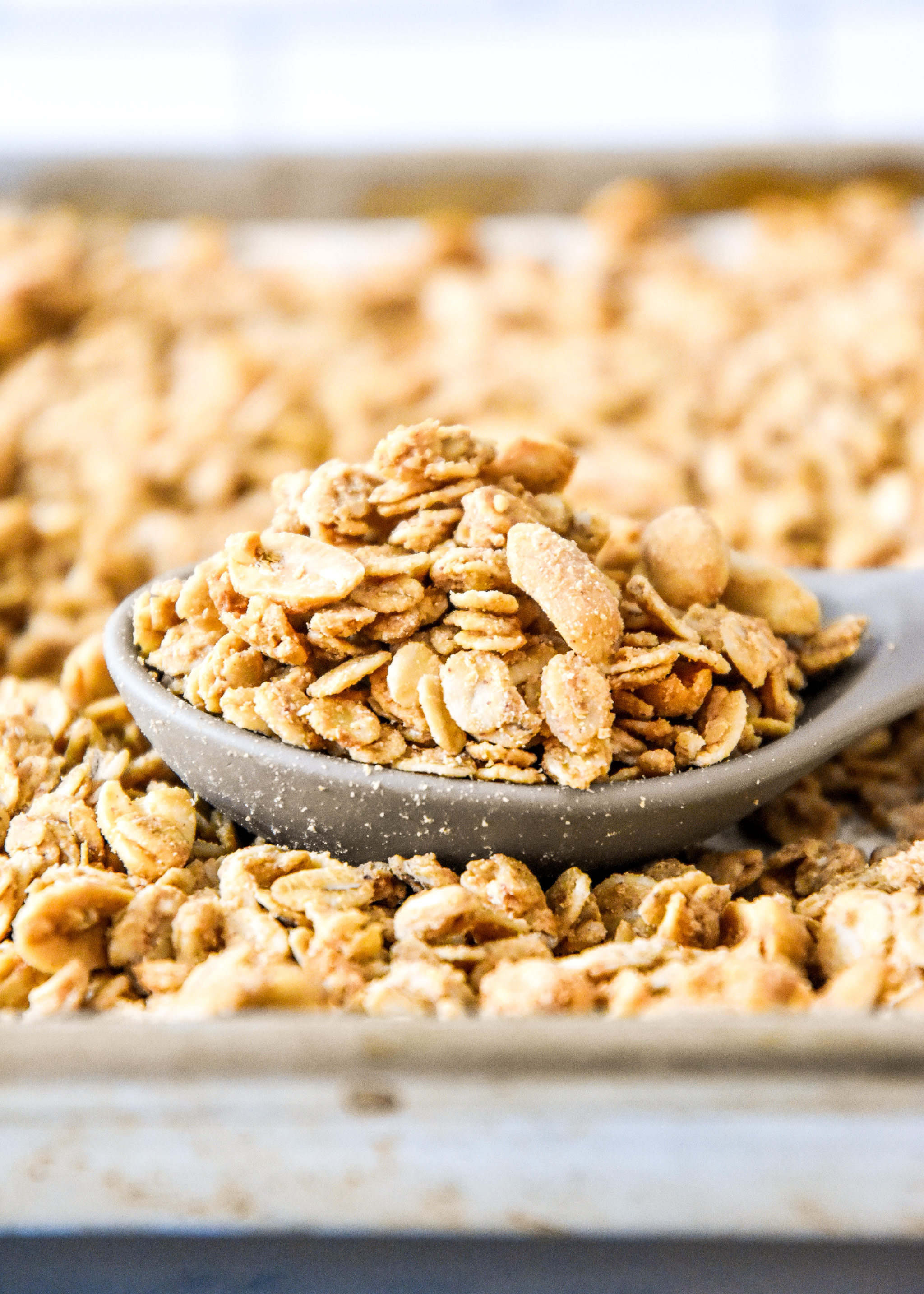 spoonful of peanut butter granola on a sheet pan.