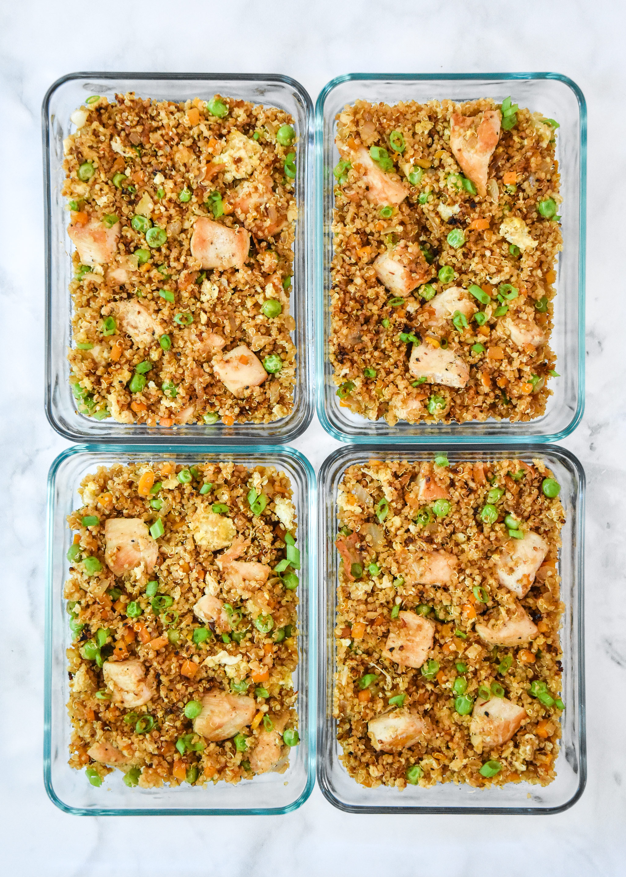 four glass meal prep containers of chicken quinoa fried rice.
