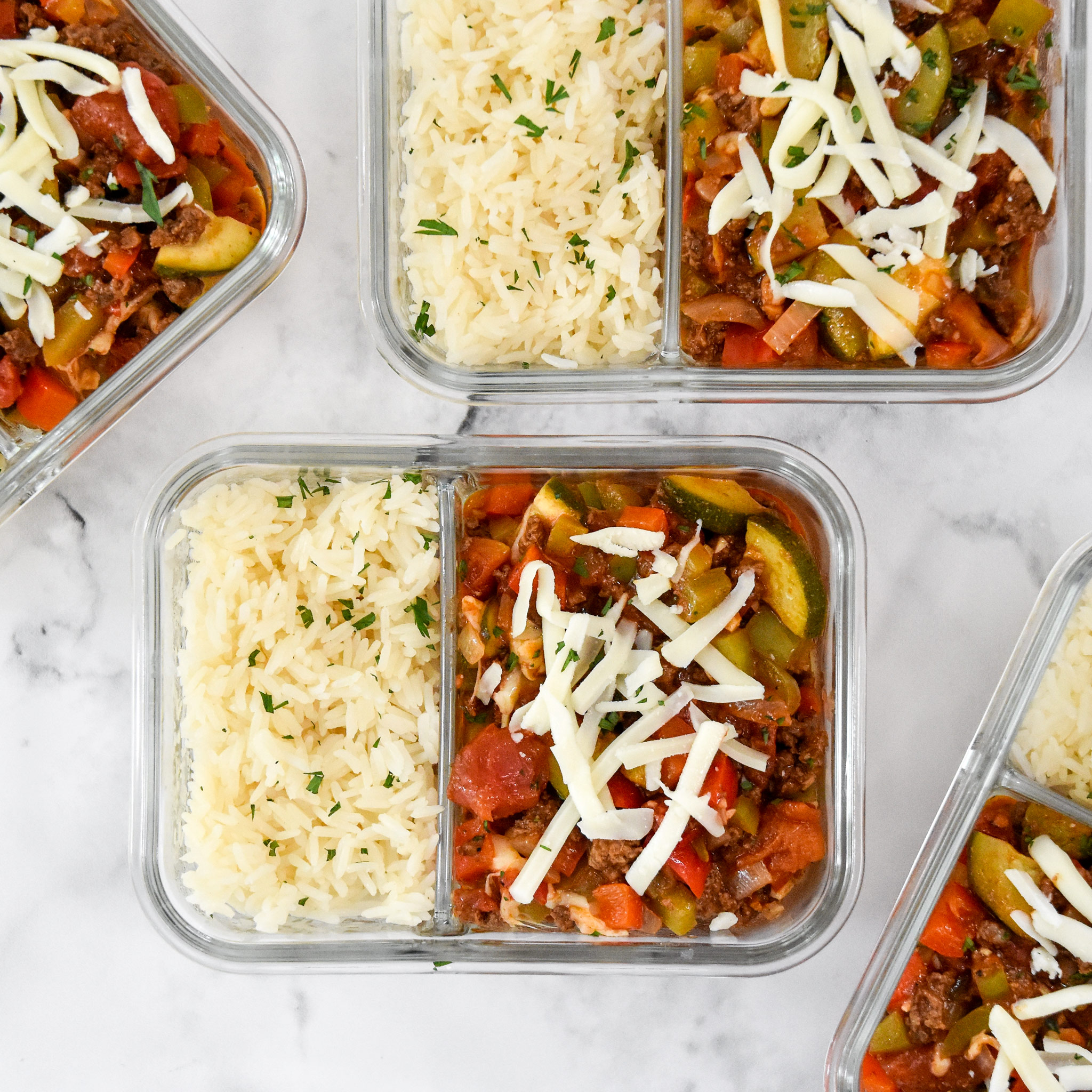 meal prep unstuffed pepper bowls in glass 2 compartment containers with cheese on top.