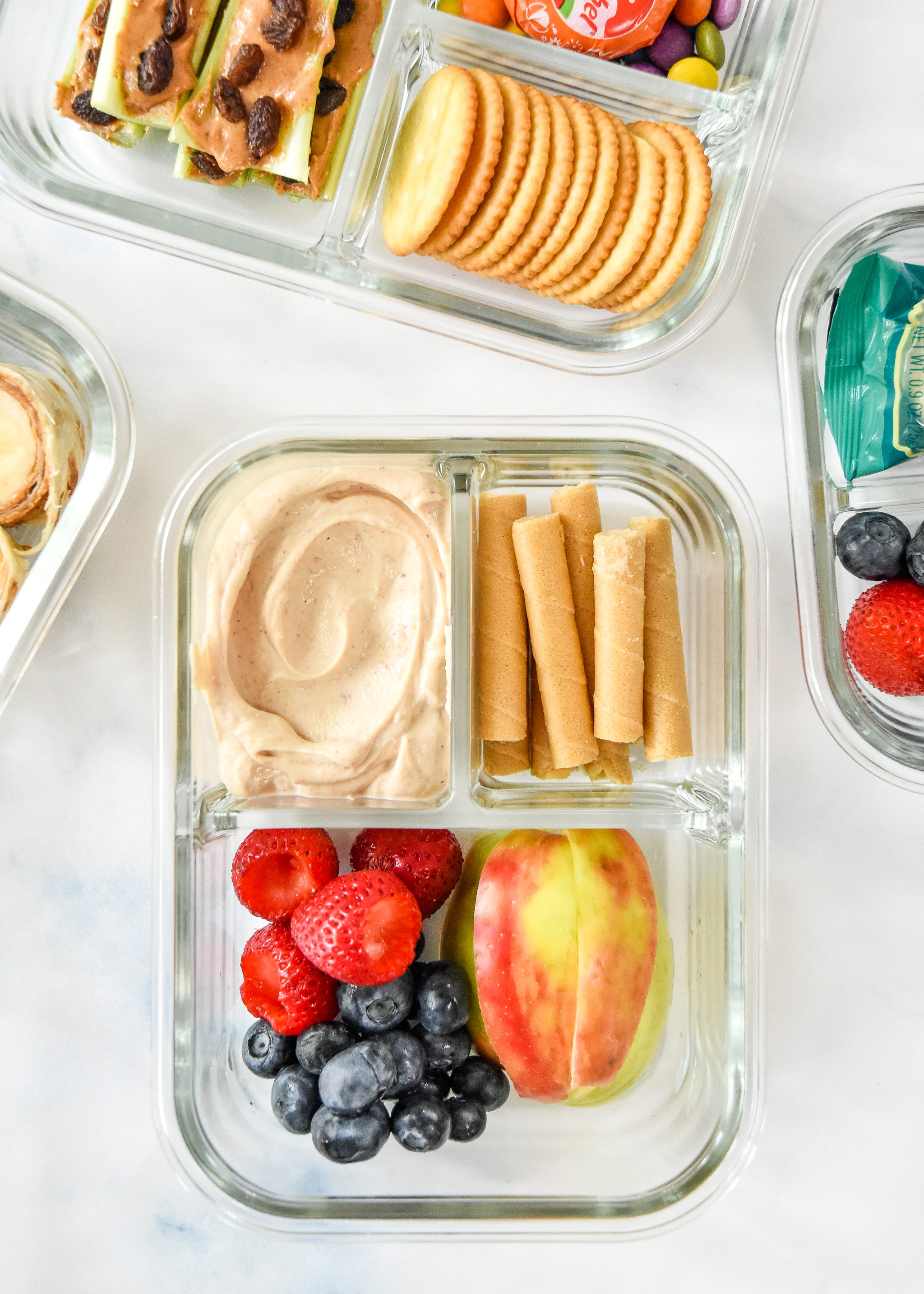 peanut butter yogurt dip with fruit and wafers in a glass meal prep container.