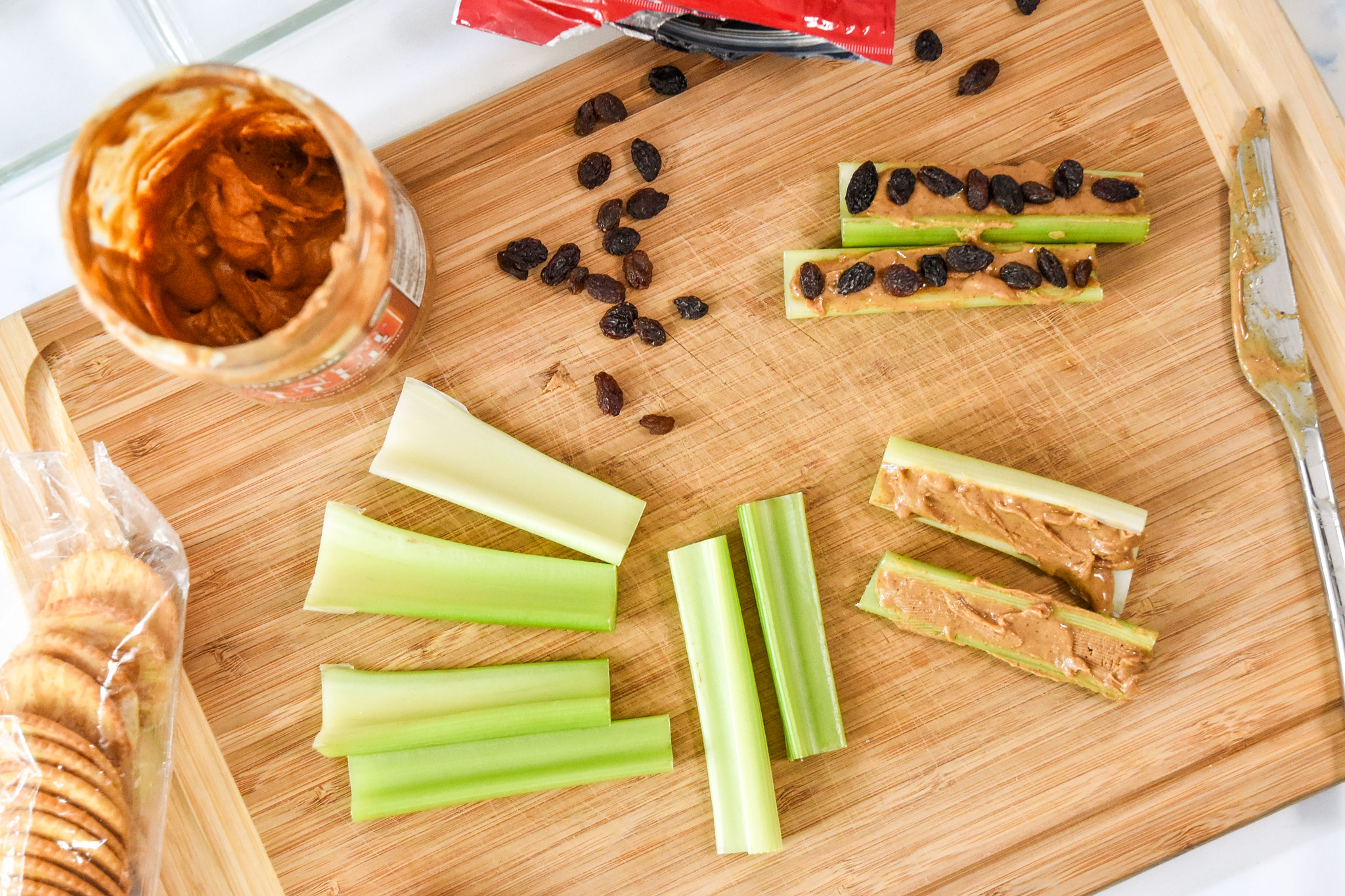 assembling ants on a log with celery, peanut butter and raisins on a cutting board.
