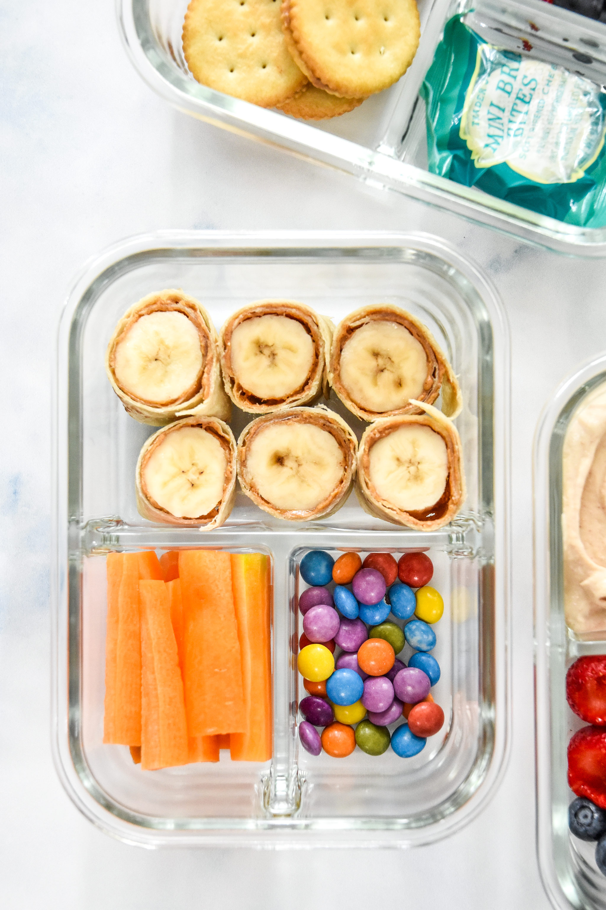 banana roll ups with carrot sticks and chocolate candies in a glass meal prep container.