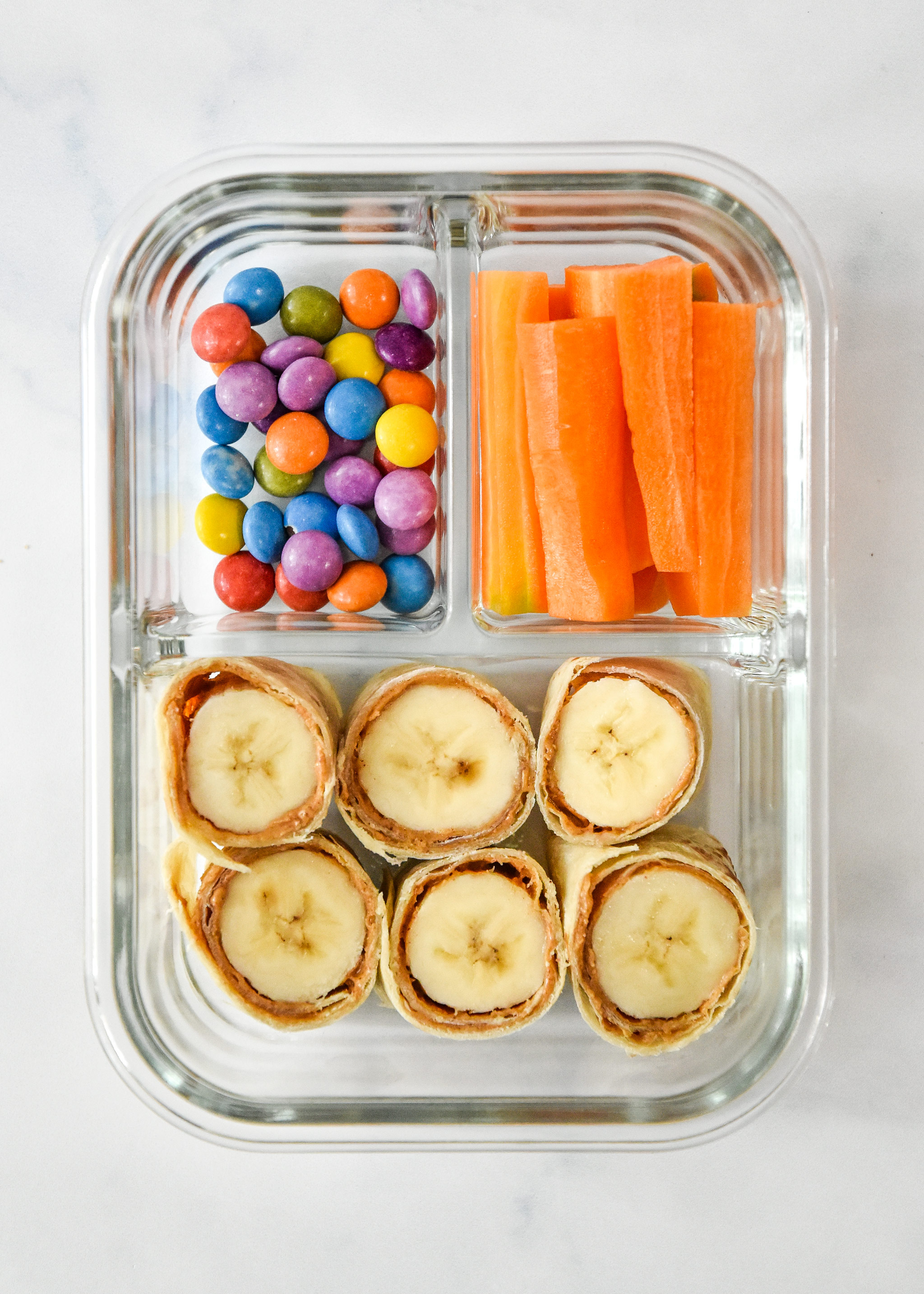 pb banana roll ups with carrot sticks and chocolate candies in a glass meal prep container.